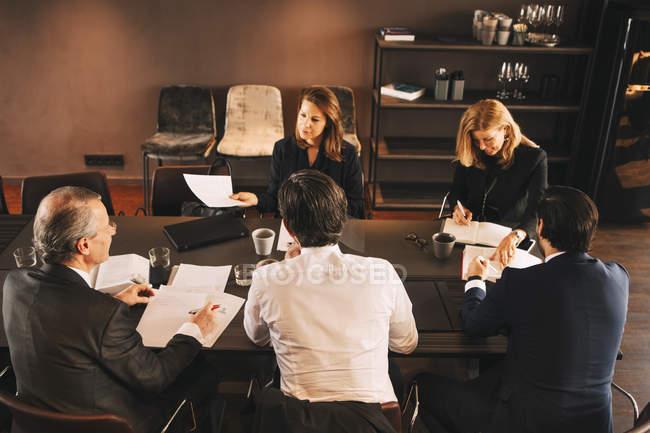 Vue en angle élevé des conseillers financiers remue-méninges dans la salle de conseil au bureau — Photo de stock