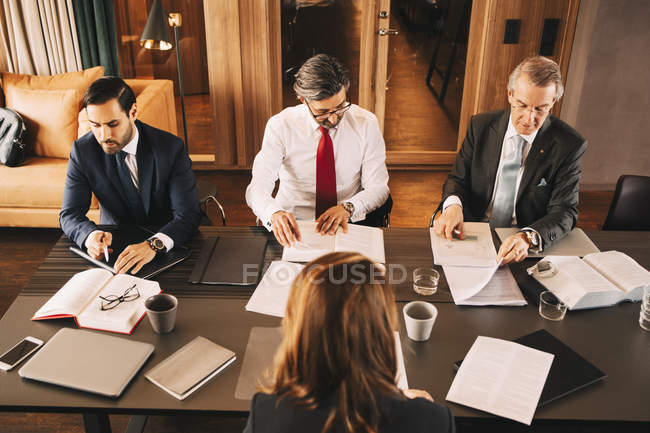 High angle view of female financial advisor planning with male lawyers in meeting at board room — Stock Photo