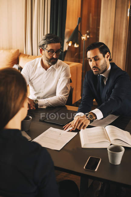 High angle view of mid adult lawyer discussing over documents with colleagues in meeting at office — Stock Photo