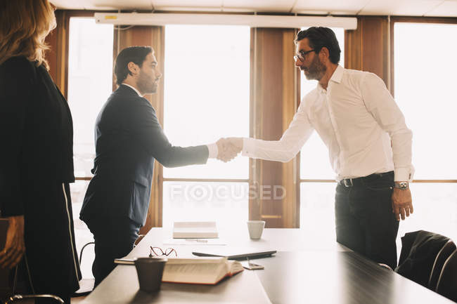 Businessman shaking hands with male lawyer after meeting in board room — Stock Photo