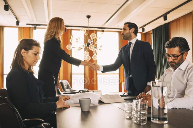 Colleghe di sesso maschile e femminile che lavorano mentre gli avvocati stringono la mano a tavola nello studio legale — Foto stock