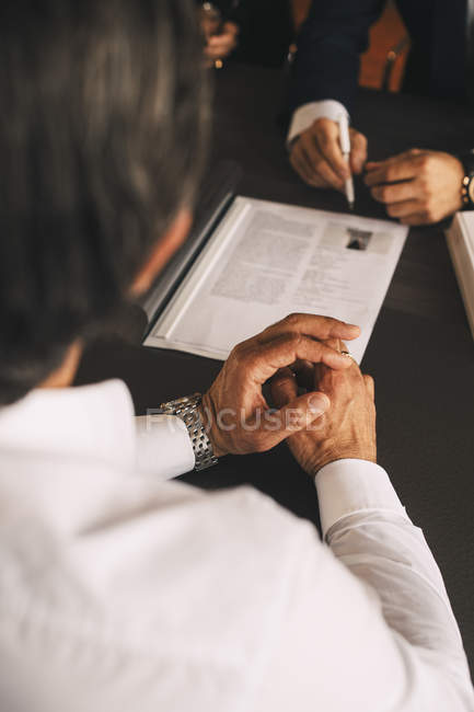High angle view of businessman discussing over document in meeting at office — Stock Photo