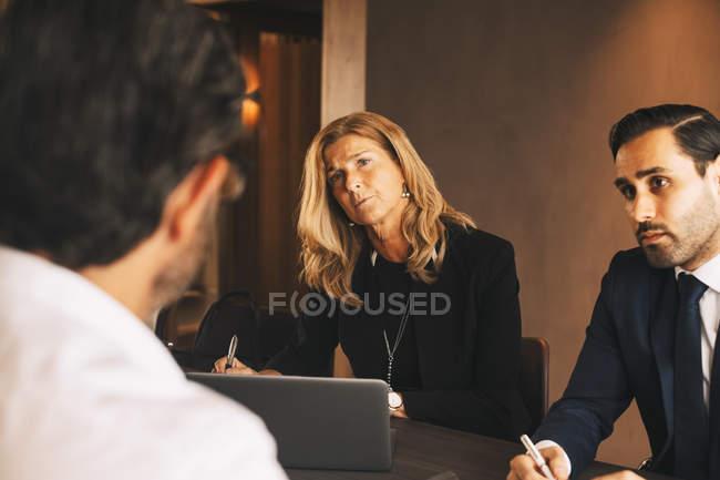Colegas legais sérios ouvindo empresário maduro durante reunião no escritório de advocacia — Fotografia de Stock