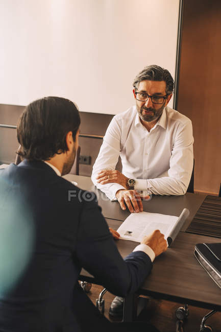 High angle view of advisor explaining document to businessman in meeting at law office — Stock Photo