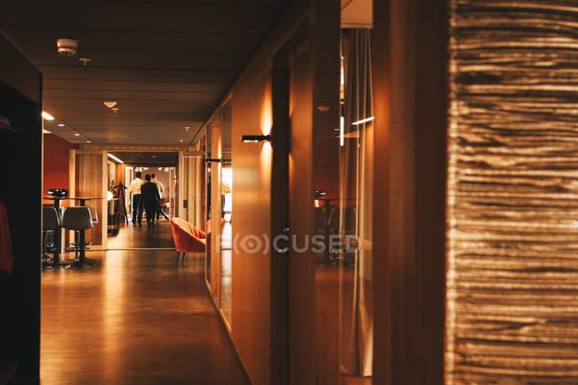 Vista distante de advogados que caminham no corredor do escritório de advocacia — Fotografia de Stock