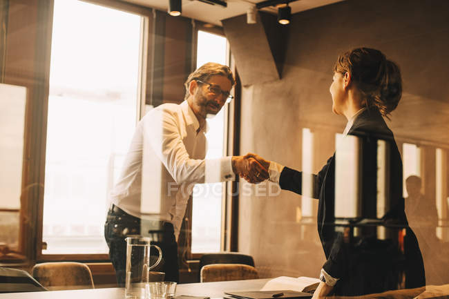 Mature customer shaking hands with female lawyer in meeting — Stock Photo
