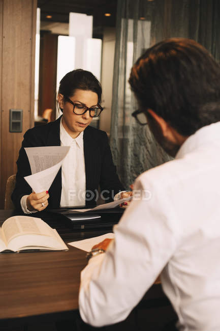 Female financial advisor reviewing documents while sitting with customer in meeting at office — Stock Photo