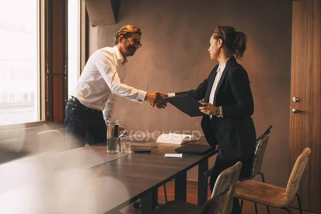 Female lawyer shaking hands with male customer after meeting at table in office — Stock Photo