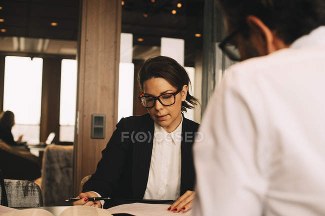 Mid adult female lawyer discussing paperwork with client at table in office — стокове фото