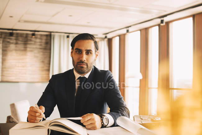 Portrait of confident lawyer with book sitting at table in law office — стокове фото