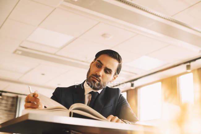 Vue en angle bas du livre de lecture du conseiller financier à la table au bureau — Photo de stock