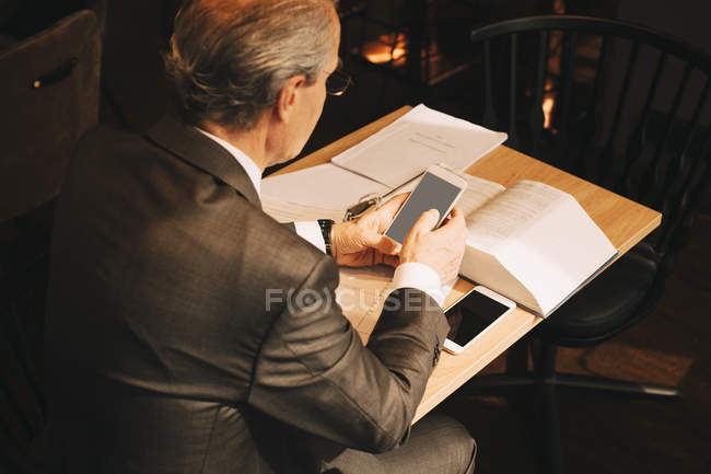 High angle view of male lawyer using smart phone while working at law office — стокове фото