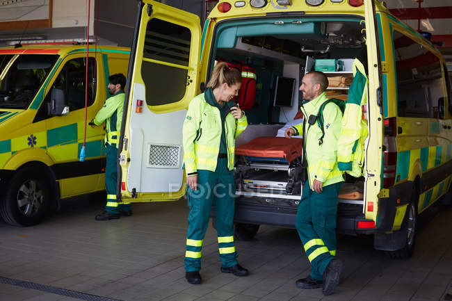 Smiling male paramedic looking at female coworker talking on walkie-talkie while standing by ambulance in parking lot. - foto de stock