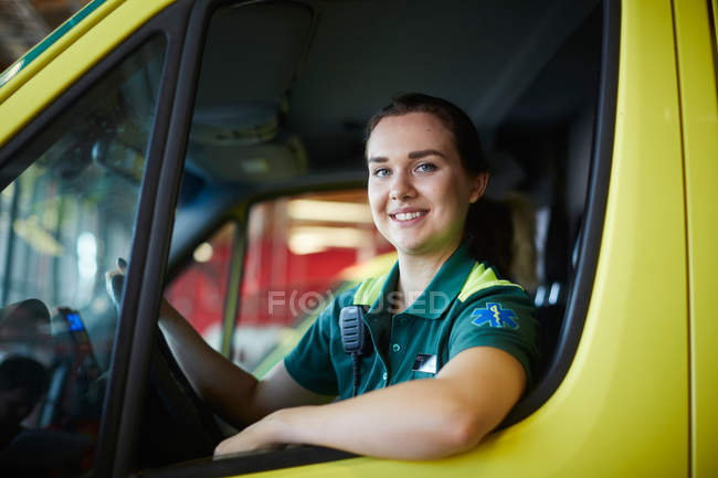 Portrait of smiling young female paramedic driving ambulance in parking lot — Stock Photo