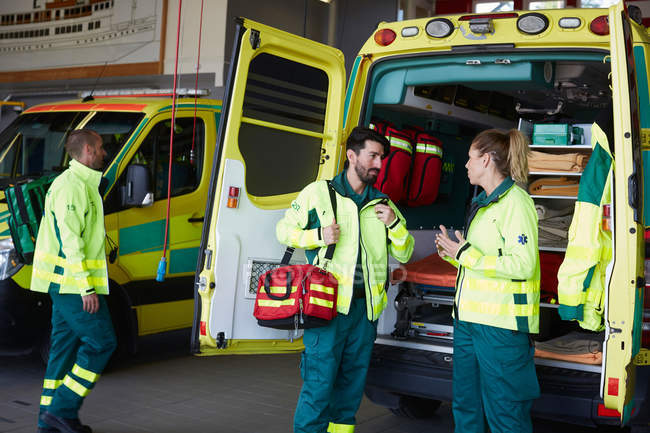 Male paramedic talking to female coworker while standing by ambulance in parking lot — Stock Photo