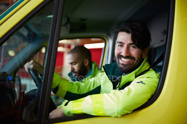 Portrait of smiling male paramedic with coworker driving ambulance in parking lot — Stock Photo