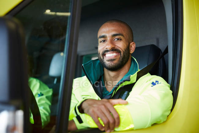Portrait of smiling male paramedic in ambulance at parking lot — Stock Photo