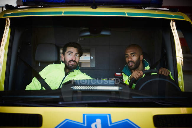 Mid adult male paramedics sitting in ambulance at parking lot — Stock Photo
