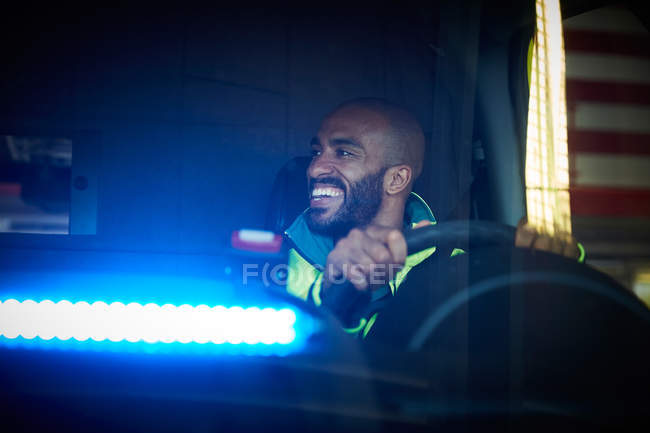 Smiling mid adult male paramedic looking away while driving ambulance in parking lot — Stock Photo
