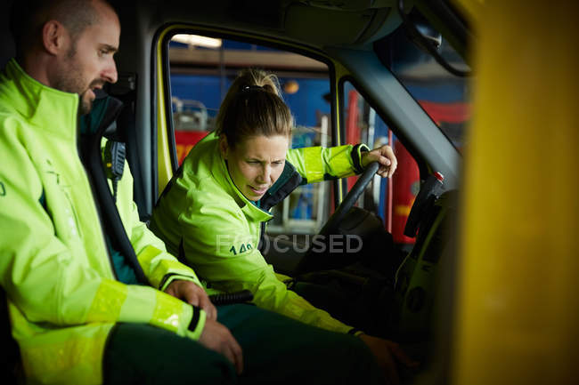 Paramedics discussing while sitting in ambulance in parking lot — Stock Photo