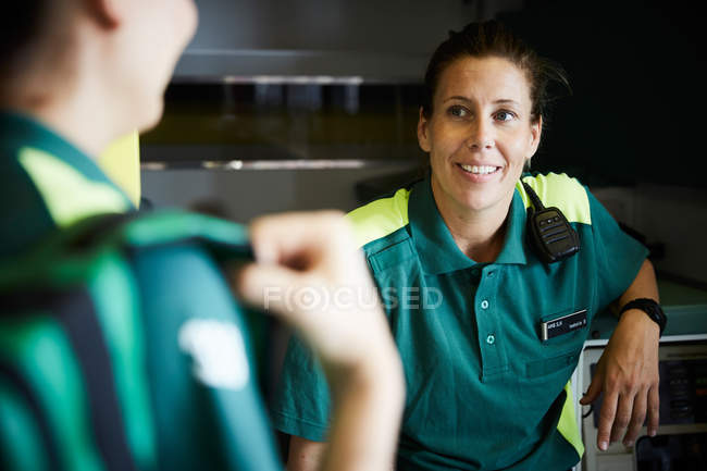 Female paramedics discussing while sitting in ambulance — Stock Photo