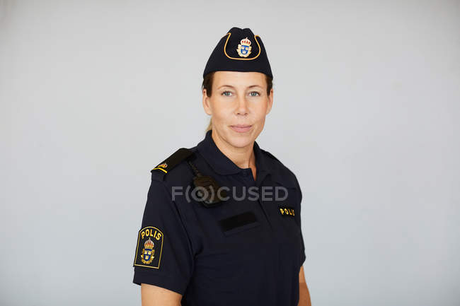 Portrait of policewoman in uniform standing against white background — Stock Photo