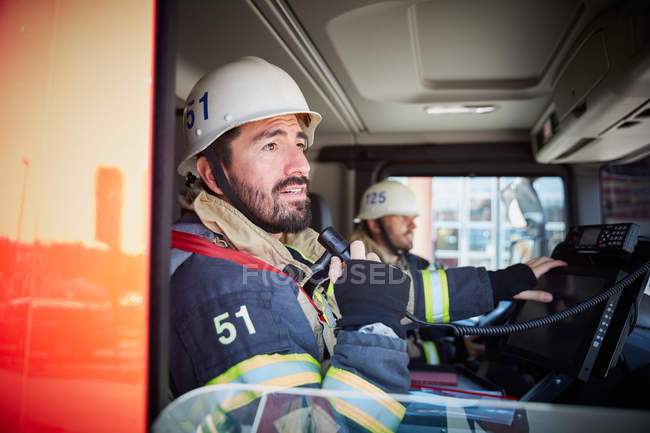 Mid adult firefighter talking on microphone while sitting with coworker in fire truck — Stock Photo