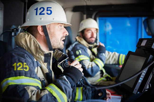 Vigile del fuoco che parla al microfono mentre si siede con il collega in motore di fuoco — Foto stock