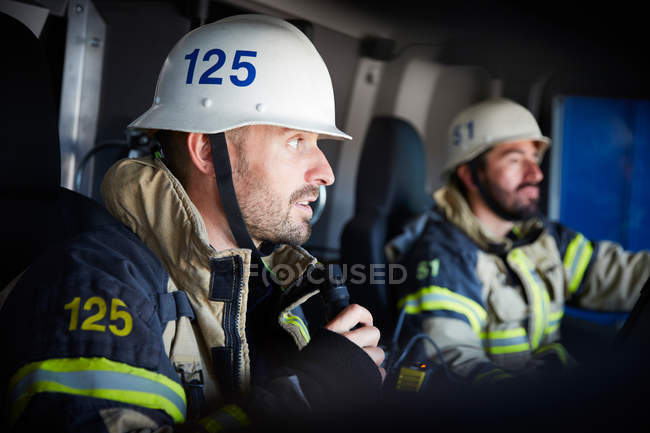 Firefighter talking on microphone while sitting with coworker in fire engine — Stock Photo