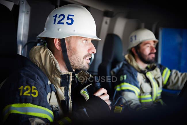 Feuerwehrmann spricht am Mikrofon, während er mit Kollegen im Feuerwehrauto sitzt — Stockfoto