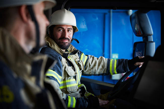 Firefighter looking at coworker while sitting in fire truck — Stock Photo