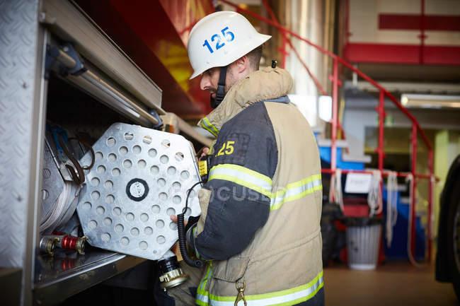 Вид сбоку пожарного, тушащего огонь в пожарной машине на станции — стоковое фото