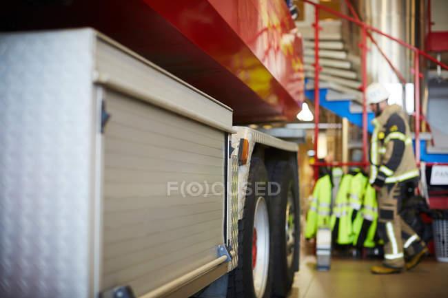 Обрезанное изображение пожарной машины с работником на заднем плане в пожарной части — стоковое фото