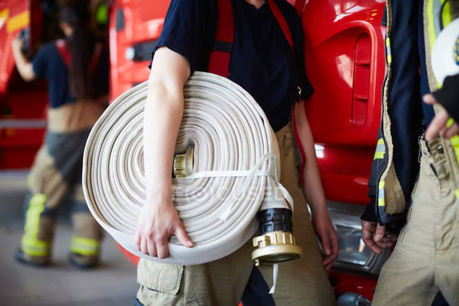 Midsection of female firefighter holding rolled up fire hose while standing with coworker at fire station — Stock Photo