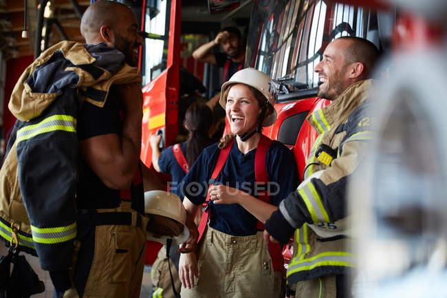 Glückliche Feuerwehrleute unterhalten sich beim Stehen gegen Feuerwehrauto am Feuerwehrhaus — Stockfoto