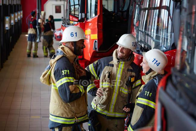 Los trabajadores sonreían mientras se oponían al motor de bomberos en la estación de bomberos. - foto de stock