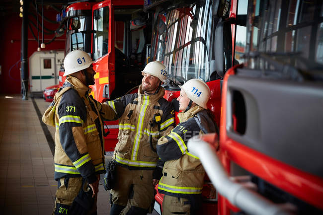 Group of firefighters talking while standing against fire engine at fire station — Stock Photo