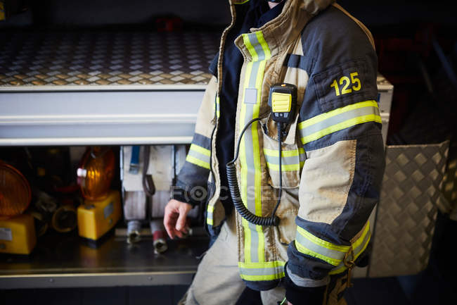 Midsection of firefighter with walkie-talkie walking at fire station — Stock Photo