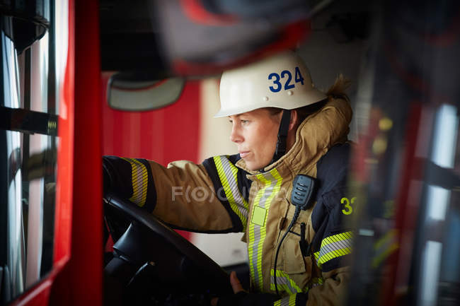 Female firefighter wearing helmet sitting in fire truck at fire station — Stock Photo