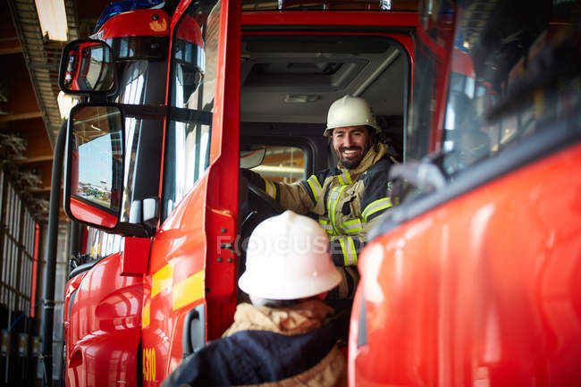 Smiling firefighter talking to coworker while sitting in fire truck at fire station — Stock Photo