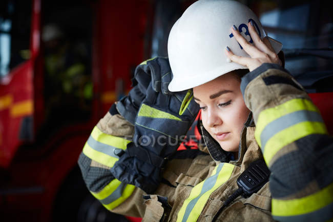 Female firefighter wearing helmet while looking down at fire station — Stock Photo