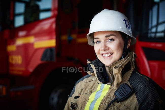 Portrait of smiling female firefighter in helmet at fire station — Stock Photo