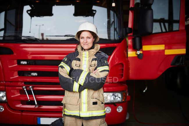 Retrato de bombeiro feminino confiante de pé com braços cruzados contra o motor de incêndio na estação de incêndio — Fotografia de Stock