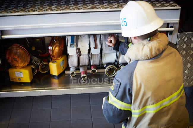 Вид пожарного, тушившего пожар в двигателе пожарной части — стоковое фото