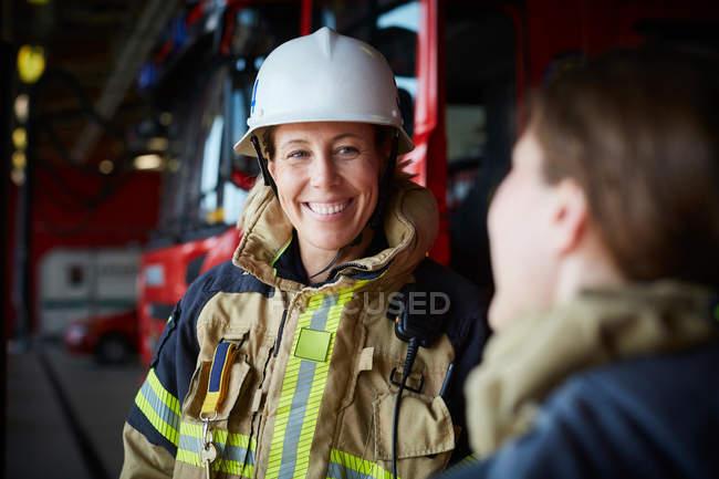Lächelnde Feuerwehrfrau blickt Kollegin im Feuerwehrhaus an — Stockfoto