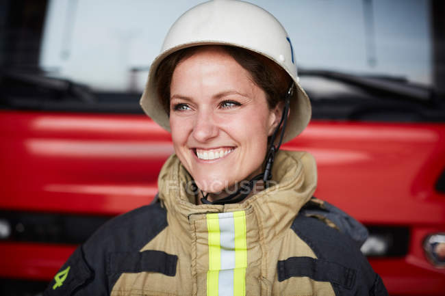 Smiling female firefighter wearing helmet looking away in fire station — Stock Photo