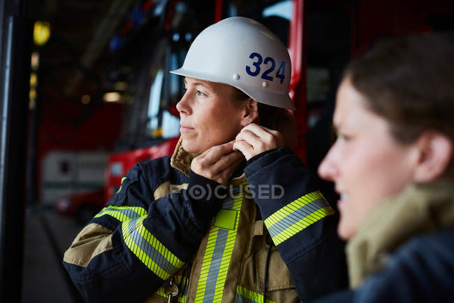 Female firefighter wearing helmet while standing with coworker in fire station — Stock Photo