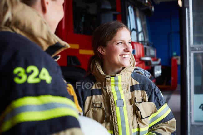 Sorrindo bombeiro feminino de pé com colega de trabalho em estação de incêndio — Fotografia de Stock