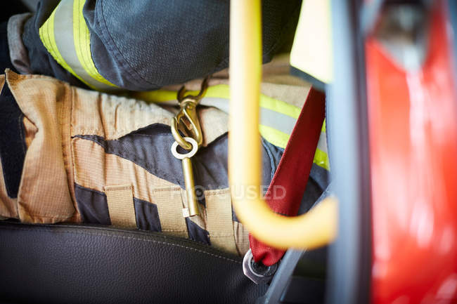 Midsection of firefighter with key ring sitting in fire truck — Stock Photo