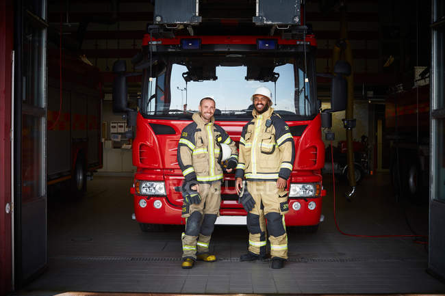 Portrait of firefighters standing in front of fire engine at fire station — Stock Photo